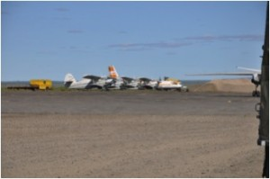 Chokurdakh airfield populated with Antanov (AN-2, AN-4?, AN-24) aircraft as well as a MI-8 helicopter. The wingtip to the right is our (cargo-)aircraft (Antanov AN-26-100) with luggage self-loading (Photo: M. Schaepman, July 2013).